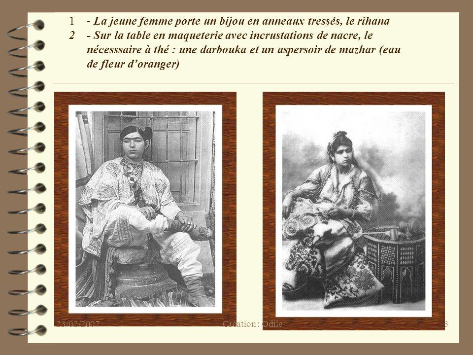 23 1- La jeune femme porte un bijou en anneaux tressés, le rihana 2- Sur la table en maqueterie avec incrustations de nacre, le nécesssaire à thé : un