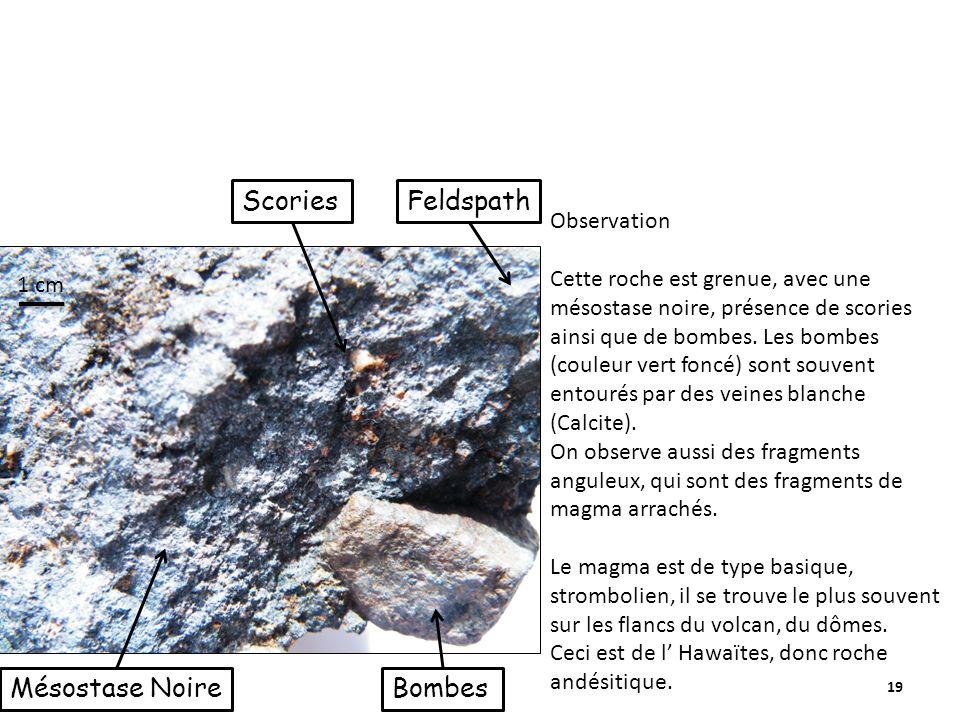 19 ScoriesFeldspath BombesMésostase Noire Observation Cette roche est grenue, avec une mésostase noire, présence de scories ainsi que de bombes.