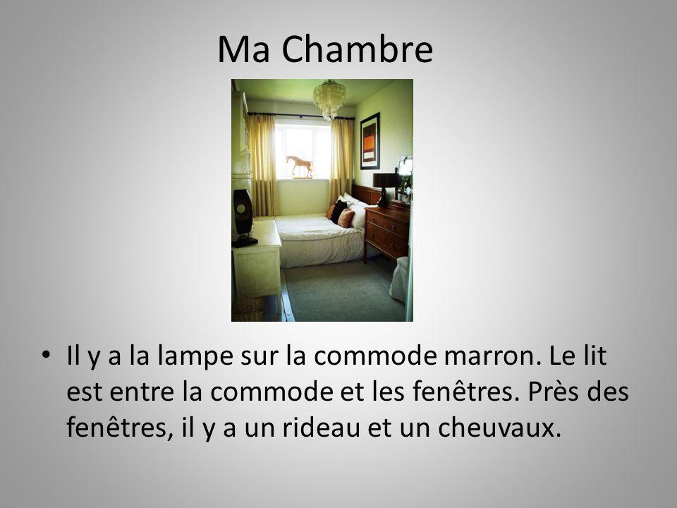 Ma Chambre Il y a la lampe sur la commode marron. Le lit est entre la commode et les fenêtres.