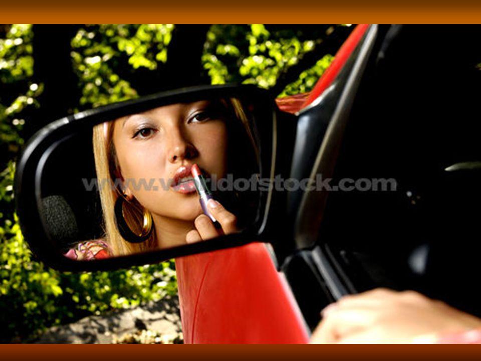 Elle se regarde dans le miroir. Elle se maquille avec du rouge à lèvres.