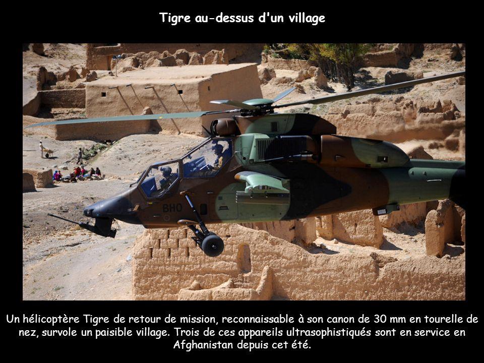 Un hélicoptère Tigre de retour de mission, reconnaissable à son canon de 30 mm en tourelle de nez, survole un paisible village. Trois de ces appareils