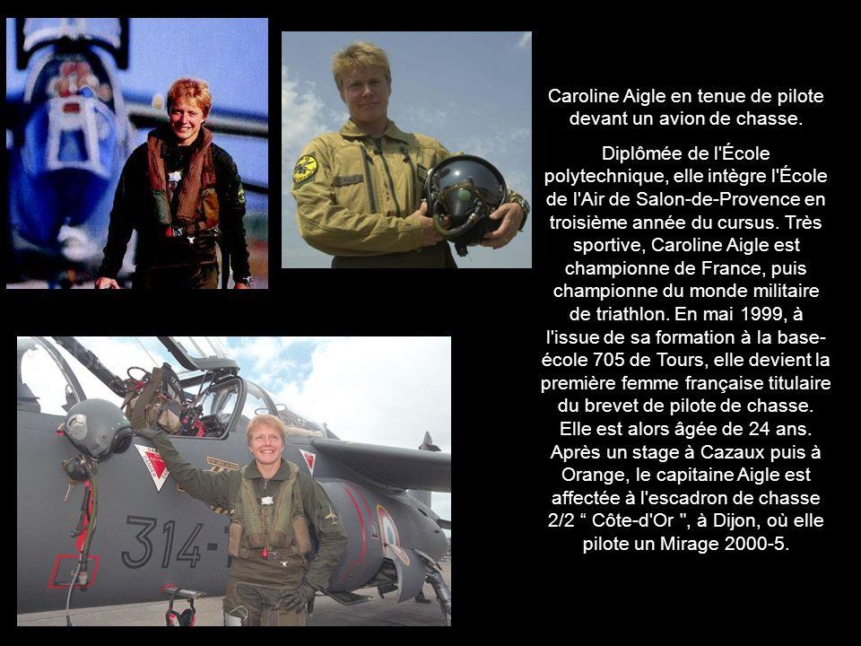 Caroline Aigle en tenue de pilote devant un avion de chasse.