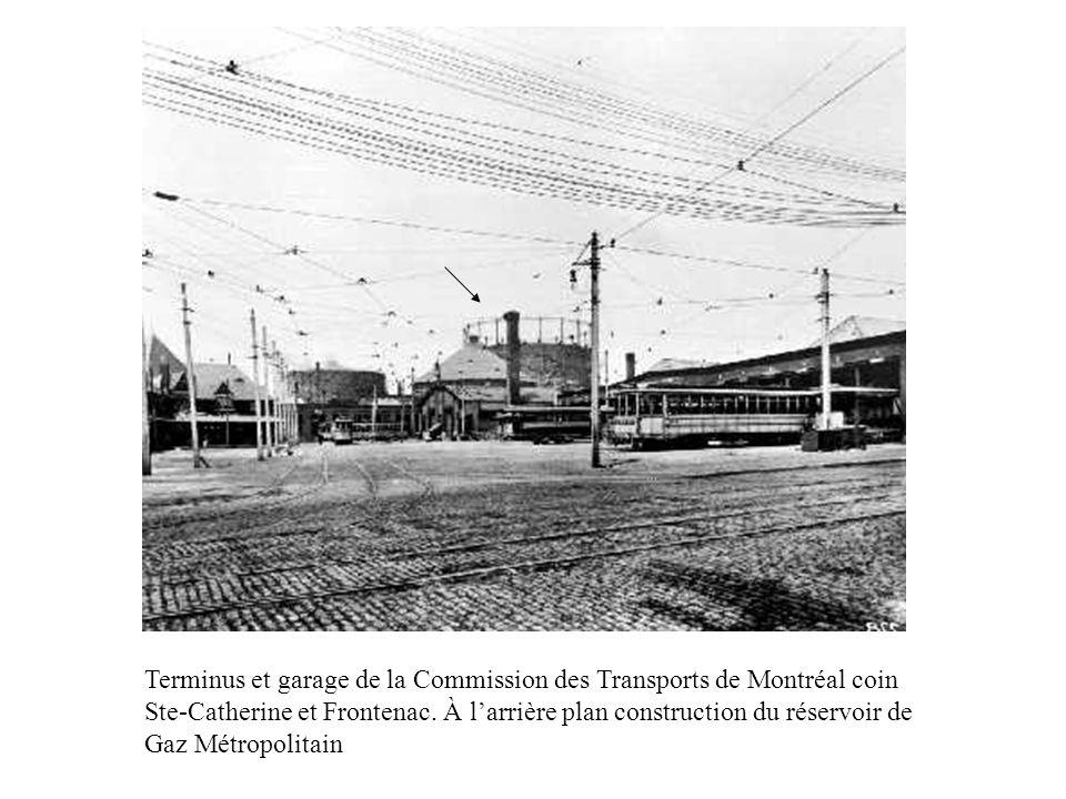 Terminus et garage de la Commission des Transports de Montréal coin Ste-Catherine et Frontenac. À larrière plan construction du réservoir de Gaz Métro