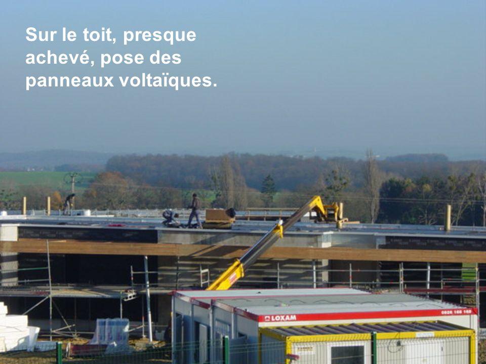 Sur le toit, presque achevé, pose des panneaux voltaïques.