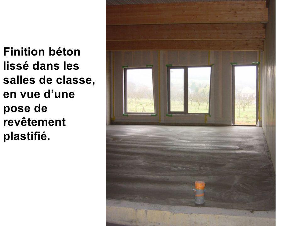 Finition béton lissé dans les salles de classe, en vue dune pose de revêtement plastifié.