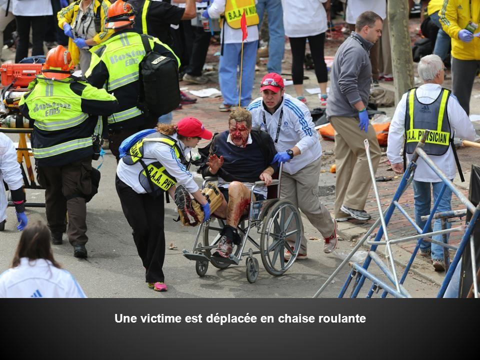 -Un homme aide une victime sur le trottoir.