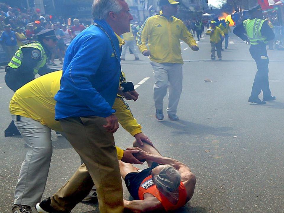 Une deuxième bombe explose (dans le fond). Un participant est projeté au sol par la première bombe près de larrivée du marathon