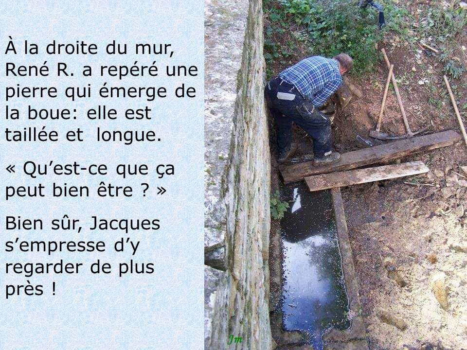 À la droite du mur, René R. a repéré une pierre qui émerge de la boue: elle est taillée et longue.