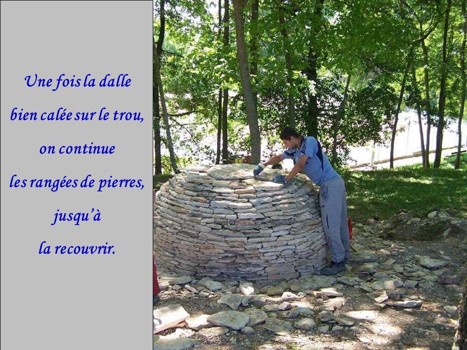 Une fois la dalle bien calée sur le trou, on continue les rangées de pierres, jusquà la recouvrir.