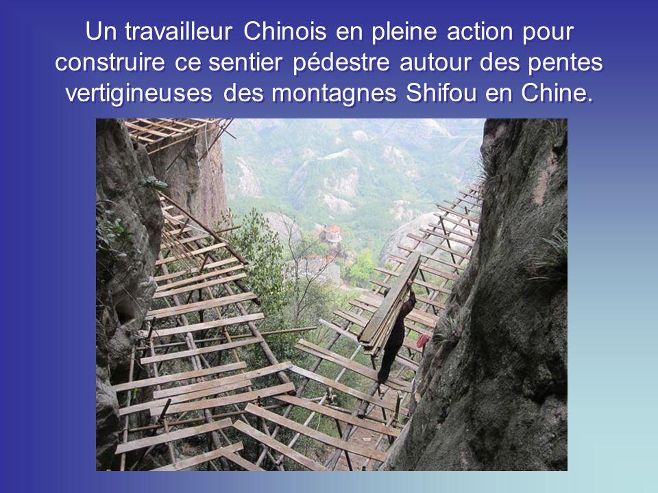 Un travailleur Chinois en pleine action pour construire ce sentier pédestre autour des pentes vertigineuses des montagnes Shifou en Chine.