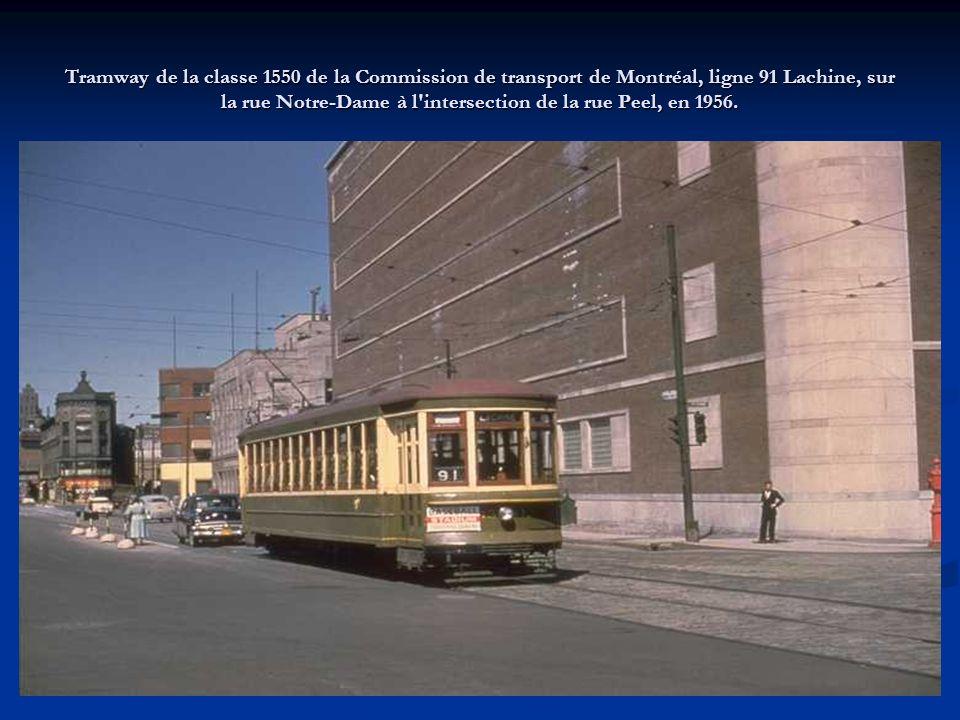Vue de plusieurs employés de la Commission de transport de Montréal effectuant des travaux de restauration des voies sur la rue Saint-Laurent, à l intersection de la rue Rachel, alors que les tramways continuent de circuler au nord, en 1955.