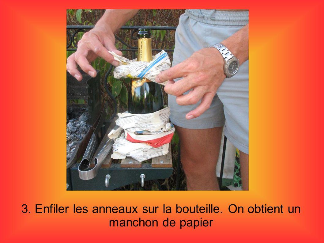 4. poser la bouteille au centre du barbecue. Recouvrir le papier de charbon de bois en tas.