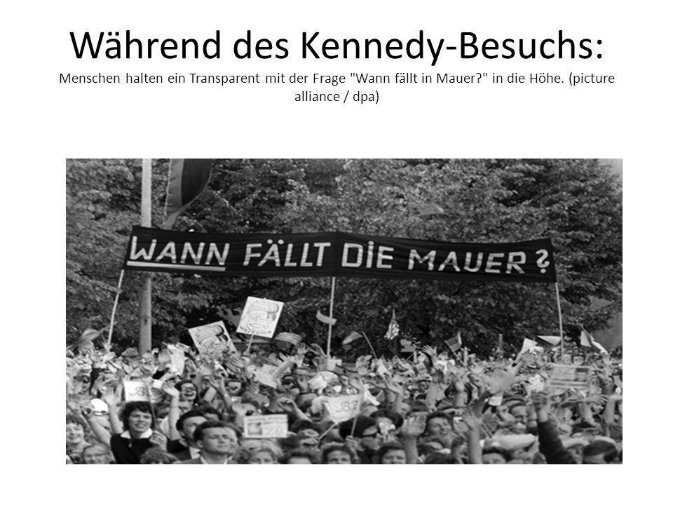 Während des Kennedy-Besuchs: Menschen halten ein Transparent mit der Frage Wann fällt in Mauer? in die Höhe.