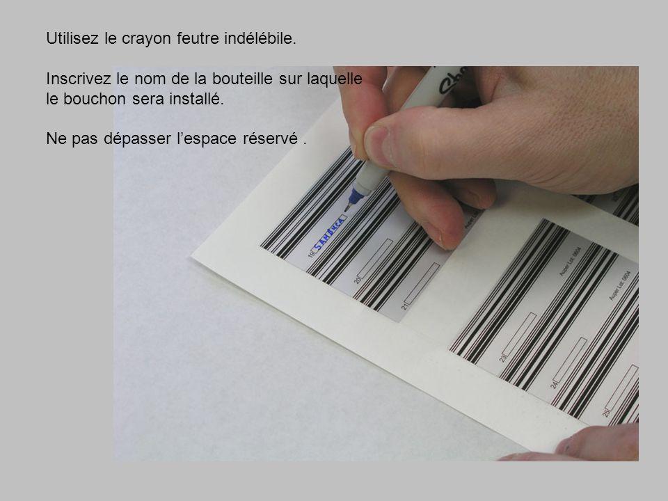 Utilisez le crayon feutre indélébile. Inscrivez le nom de la bouteille sur laquelle le bouchon sera installé. Ne pas dépasser lespace réservé.