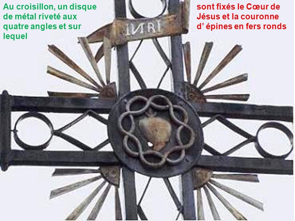 Au croisillon, un disque de métal riveté aux quatre angles et sur lequel sont fixés le Cœur de Jésus et la couronne d épines en fers ronds