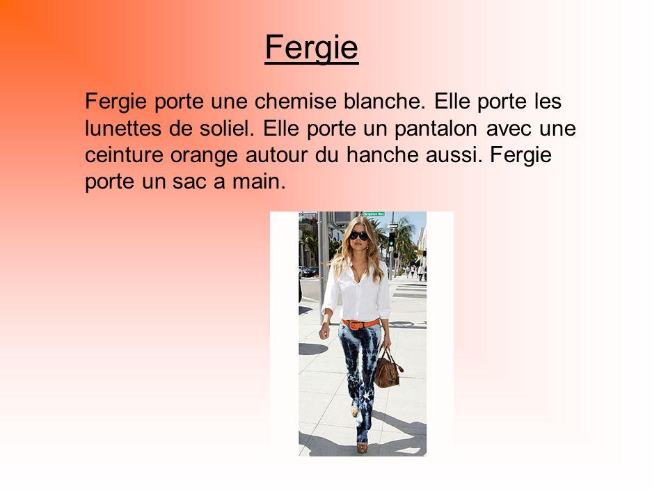 Fergie Fergie porte une chemise blanche. Elle porte les lunettes de soliel. Elle porte un pantalon avec une ceinture orange autour du hanche aussi. Fe
