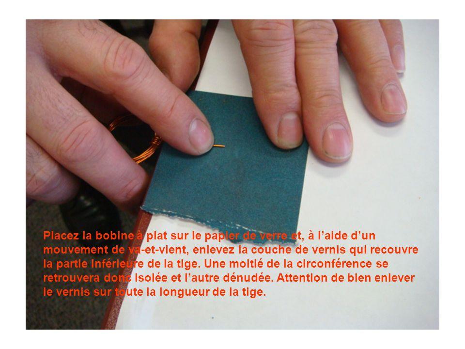 Placez la bobine à plat sur le papier de verre et, à laide dun mouvement de va-et-vient, enlevez la couche de vernis qui recouvre la partie inférieure de la tige.