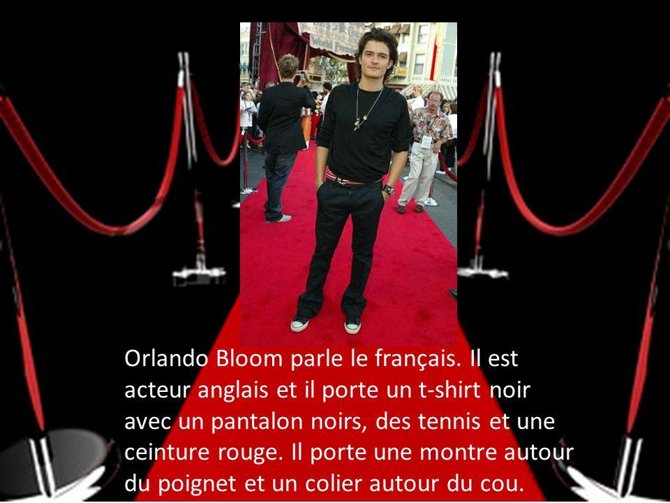 Orlando Bloom parle le français. Il est acteur anglais et il porte un t-shirt noir avec un pantalon noirs, des tennis et une ceinture rouge. Il porte