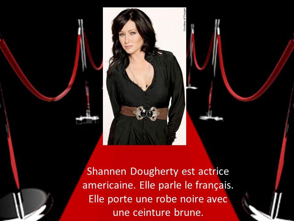 Shannen Dougherty est actrice americaine. Elle parle le français. Elle porte une robe noire avec une ceinture brune.