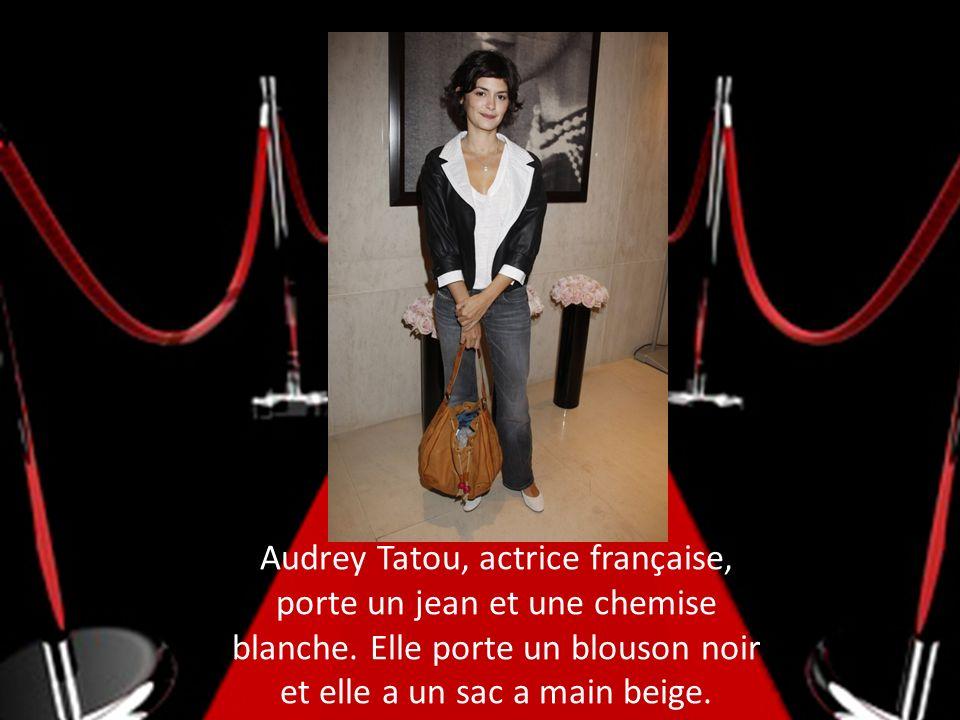 Audrey Tatou, actrice française, porte un jean et une chemise blanche. Elle porte un blouson noir et elle a un sac a main beige.