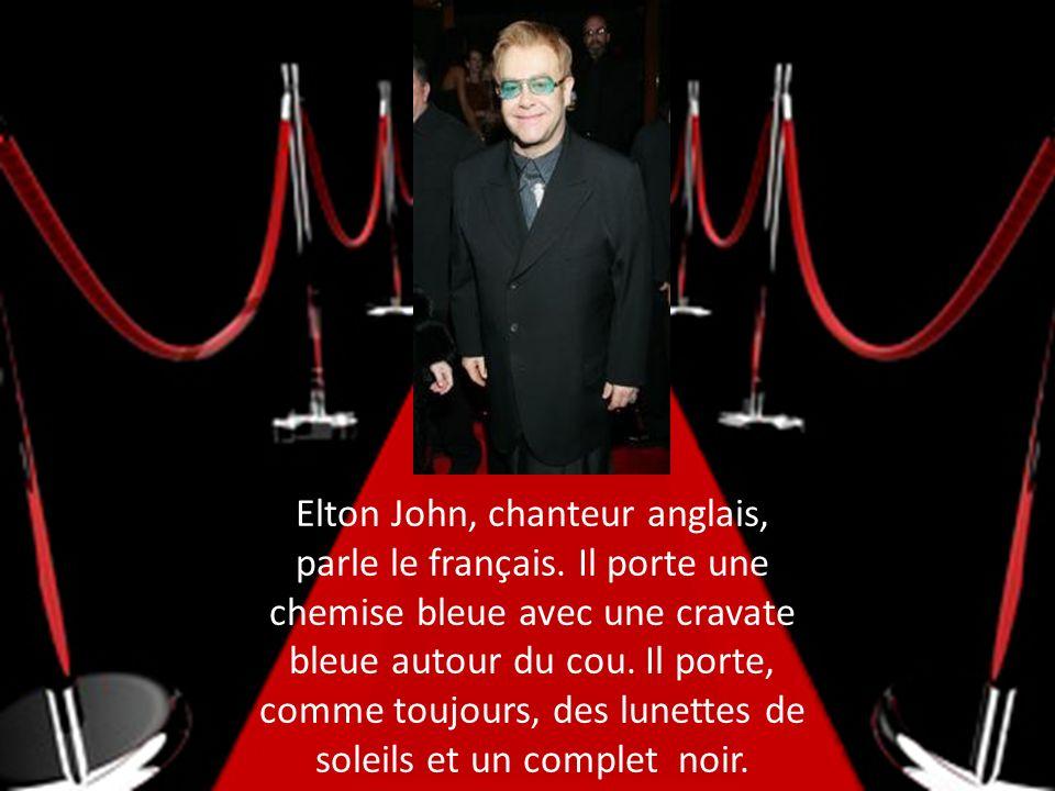 Elton John, chanteur anglais, parle le français. Il porte une chemise bleue avec une cravate bleue autour du cou. Il porte, comme toujours, des lunett