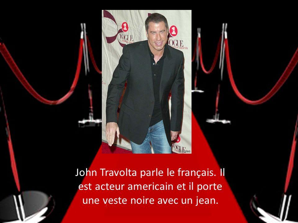 John Travolta parle le français. Il est acteur americain et il porte une veste noire avec un jean.