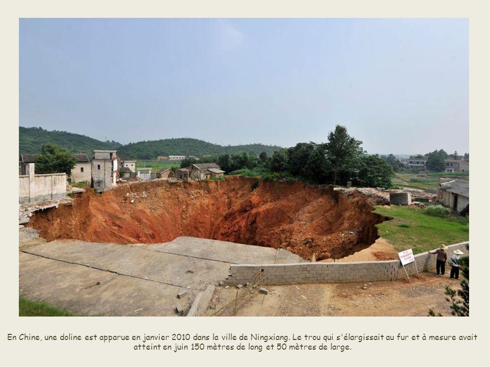 Une route cède en partie à Hefei, dans la province d'Anhui, en Chine, le 8 août 2008. Un taxi et des motos sont aspirés dans la faille.