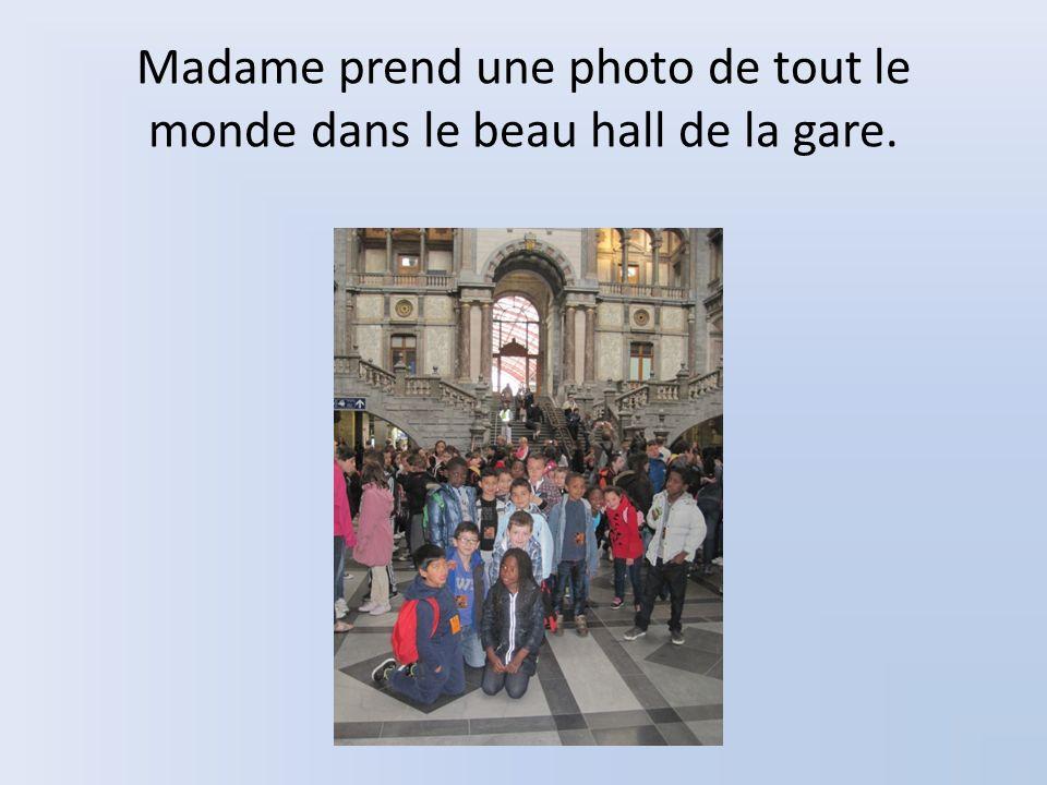 Madame prend une photo de tout le monde dans le beau hall de la gare.