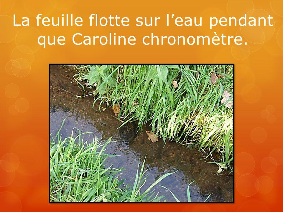 La feuille flotte sur leau pendant que Caroline chronomètre.