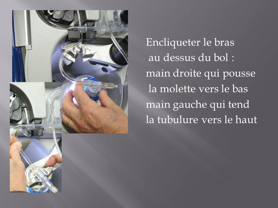 Encliqueter le bras au dessus du bol : main droite qui pousse la molette vers le bas main gauche qui tend la tubulure vers le haut