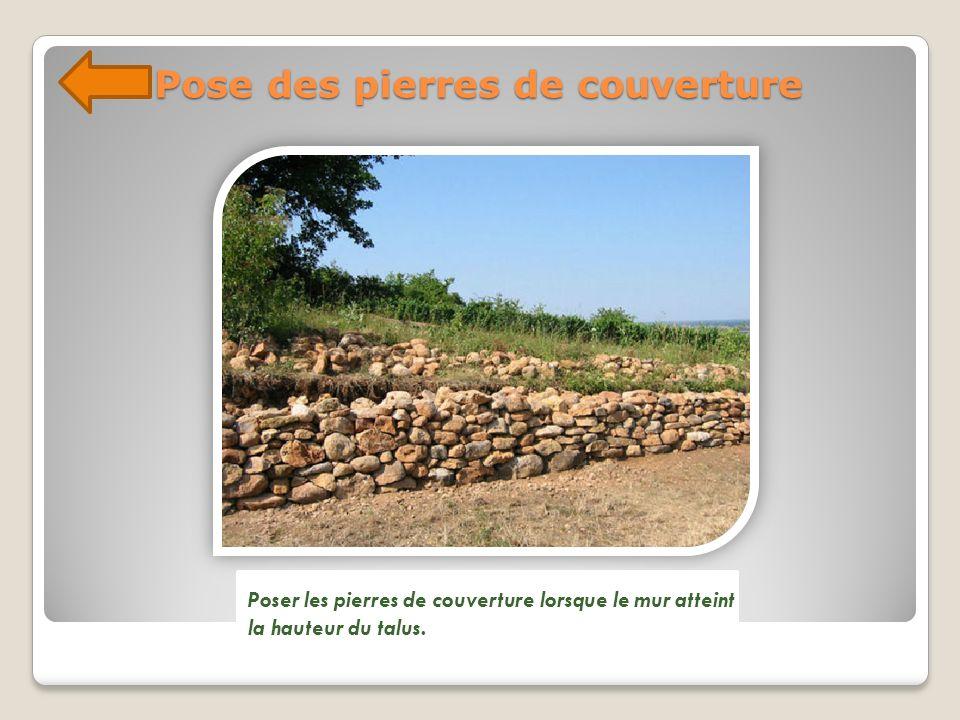 Pose des pierres de couverture Poser les pierres de couverture lorsque le mur atteint la hauteur du talus.