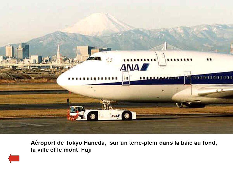 Aéroport de Tokyo Haneda, sur un terre-plein dans la baie au fond, la ville et le mont Fuji