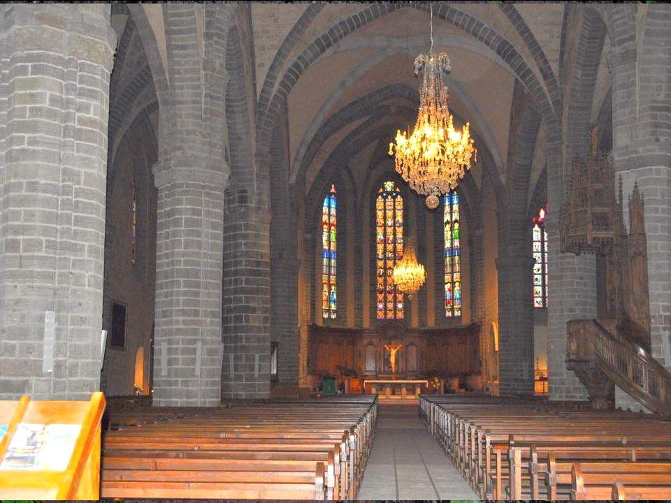 A lintérieur de léglise, la nef voûtée dogives est animée par la pierre foncée – brèche volcanique – des piliers et des arcs, qui contraste avec les enduits clairs.
