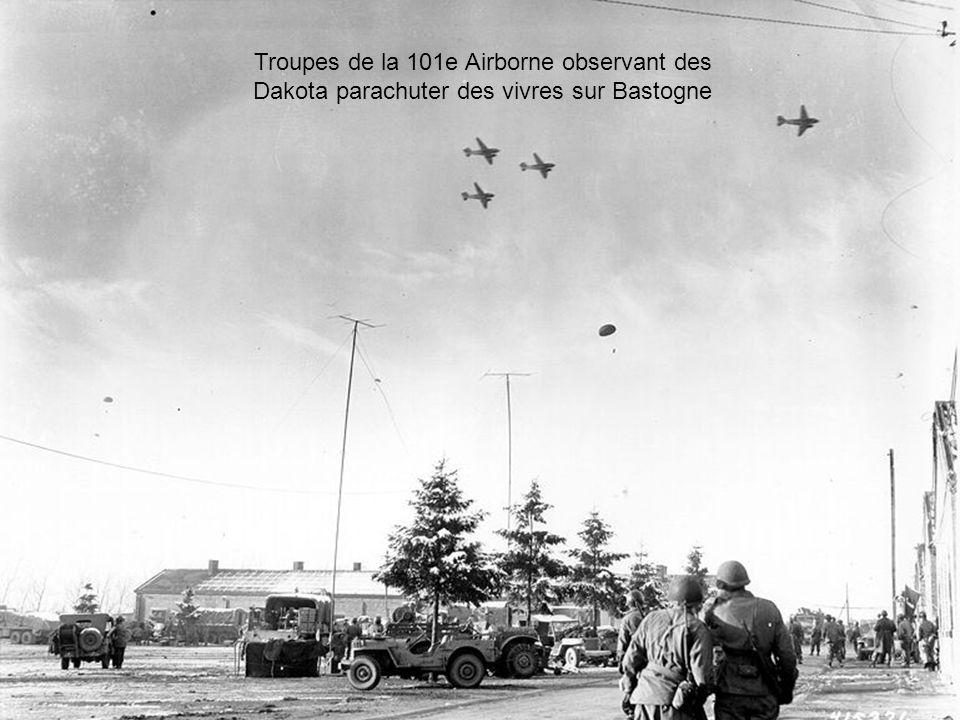 Des réfugiés Belges arrivent à Bastogne sous les yeux des troupes Américaines défendant la ville