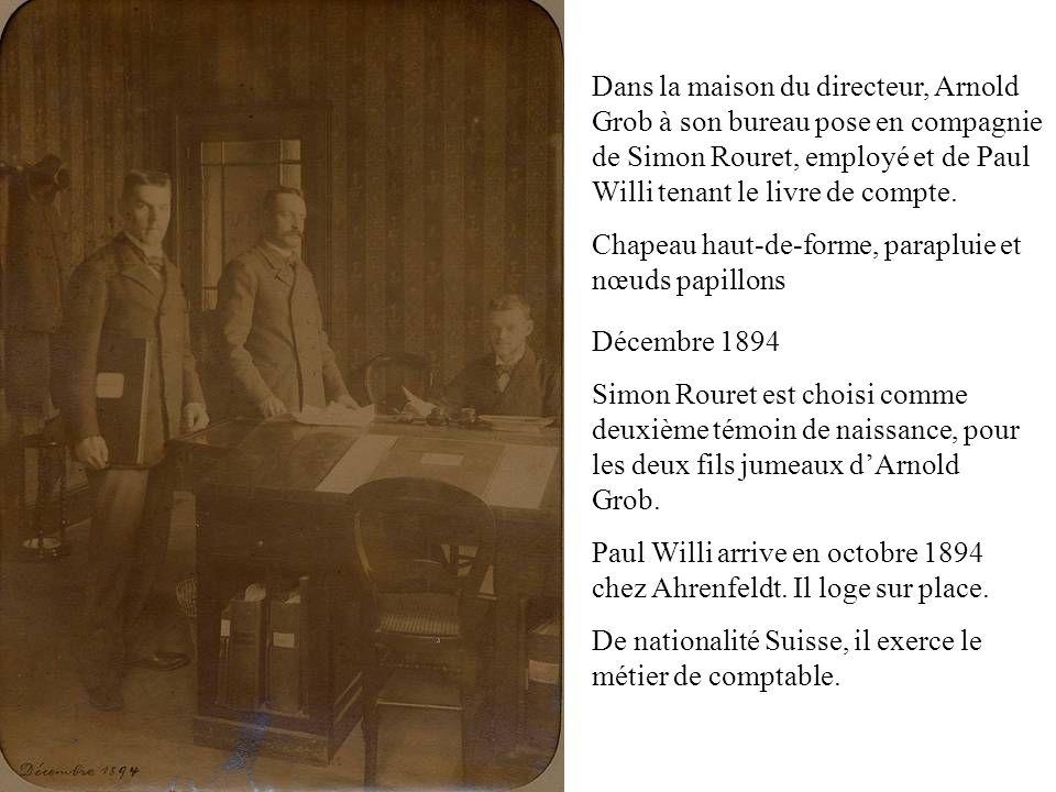 Dans la maison du directeur, Arnold Grob à son bureau pose en compagnie de Simon Rouret, employé et de Paul Willi tenant le livre de compte. Chapeau h
