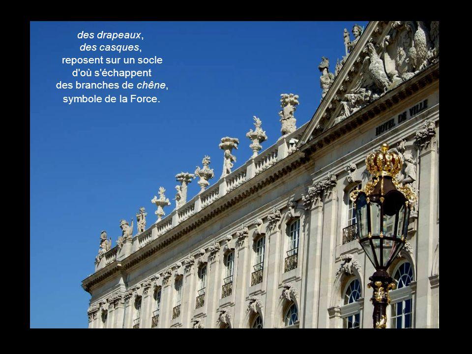 Les acrotères du balustre qui court au long de l'édifice supportent des pots à feu de dessin baroque : des palmiers, symbolisant la Victoire, la fécon