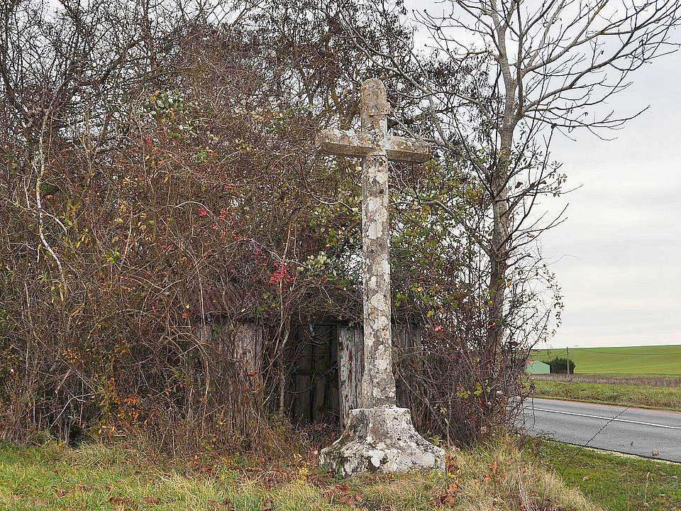 Sur une des routes pittoresques de la Nièvre, entre Clamecy et Varzy, se dresse en pleins champs cette belle croix. On devine une porte derrière : de