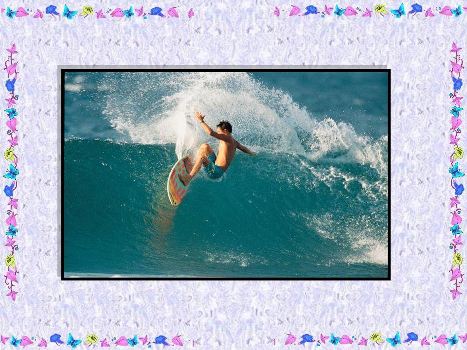 Un petit garçon, aux cheveux noirs comme lorage et tout bronzé, surfait sur les grosses vagues de locéan.