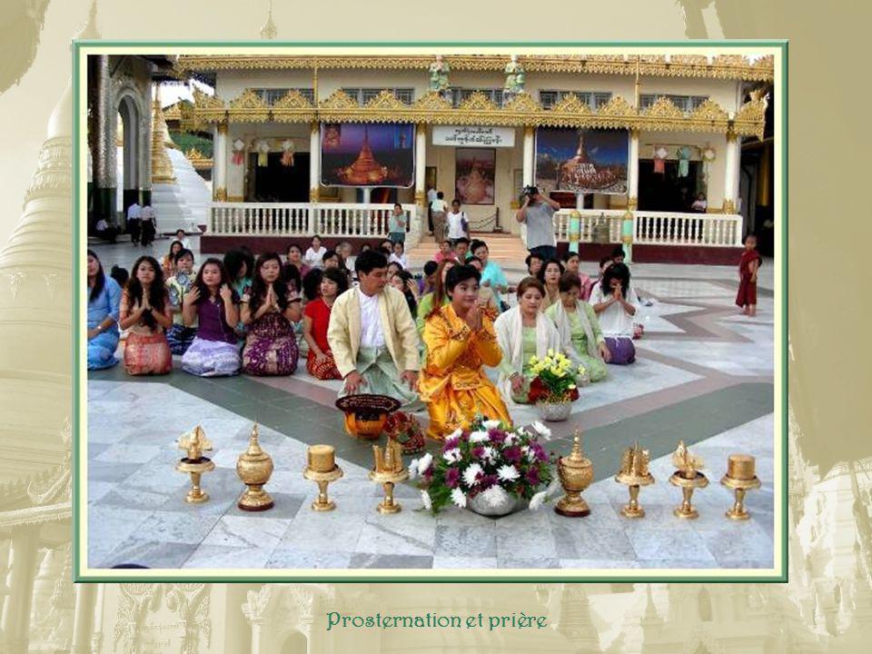 Après les hommes porteurs doffrandes, au centre, sous des parasols, le nouveau moine tout de jaune vêtu..