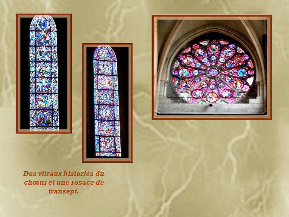 Des vitraux modernes créés par Simon de Reims pour remplacer ceux détruits durant la guerre, font contraste avec la rose du couchant réalisée à la fin