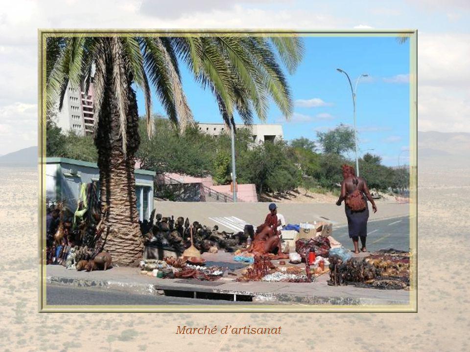 A proximité de la cour suprême, un immense stationnement se termine par un emplacement ombragé investi par les vendeurs dartisanat namibien.