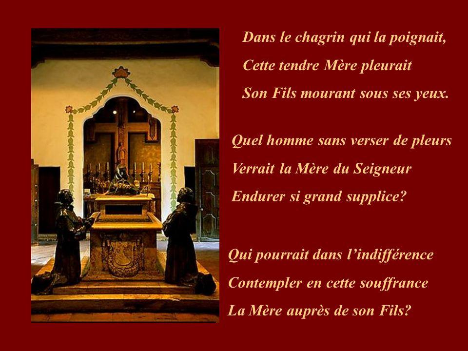 Debout, la Mère des douleurs, Près de la croix était en larmes, Quand son Fils pendait au bois. Alors, son âme gémissante, Toute triste et toute dolen