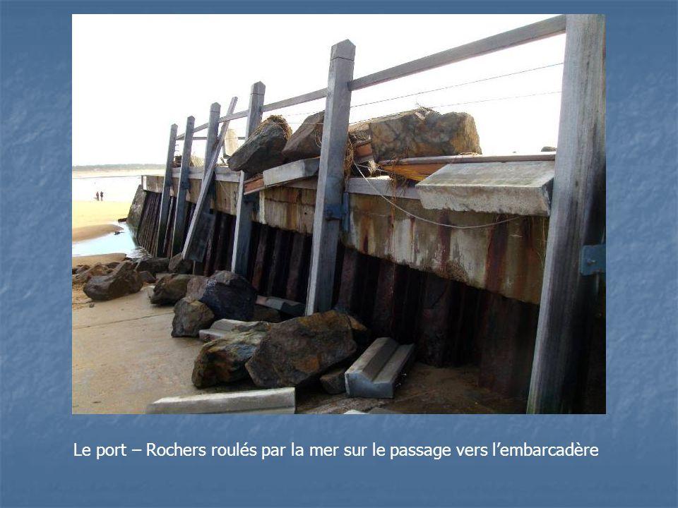 Le port – Rochers roulés par la mer sur le passage vers lembarcadère