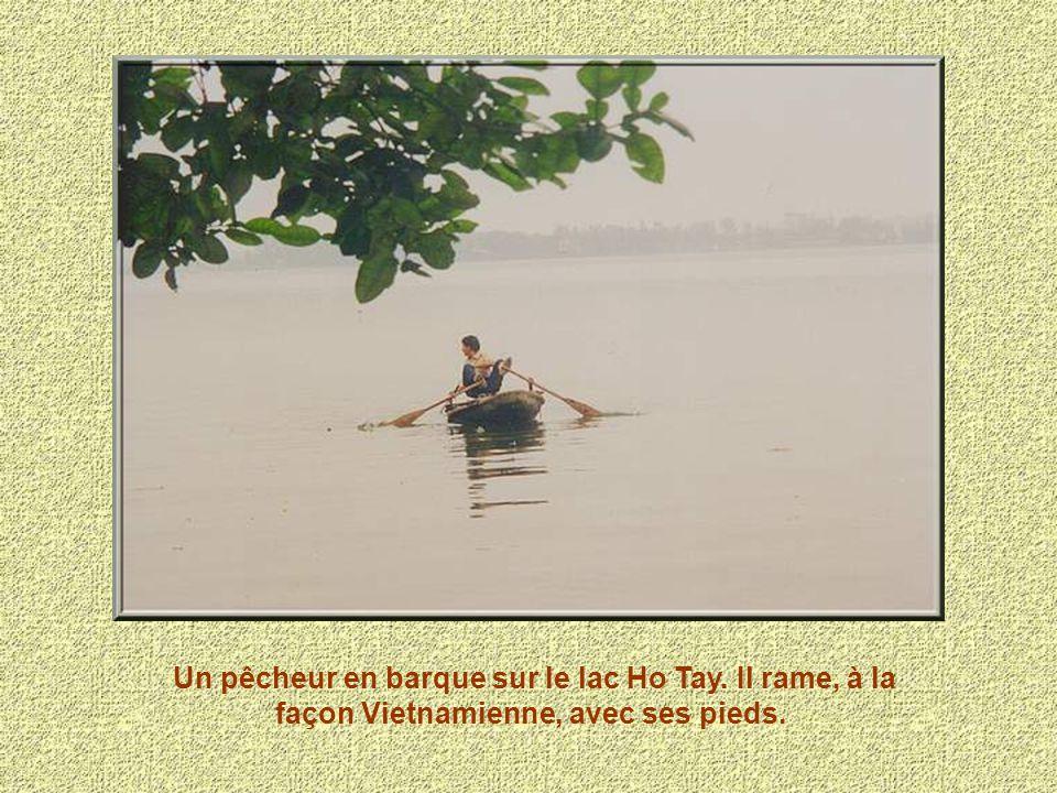 Un pêcheur en barque sur le lac Ho Tay. Il rame, à la façon Vietnamienne, avec ses pieds.