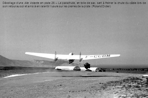Décollage dune Aile Volante en piste 26 – Le parachute, en toile de sac, sert à freiner la chute du câble lors de son retour au sol et ainsi à en rale