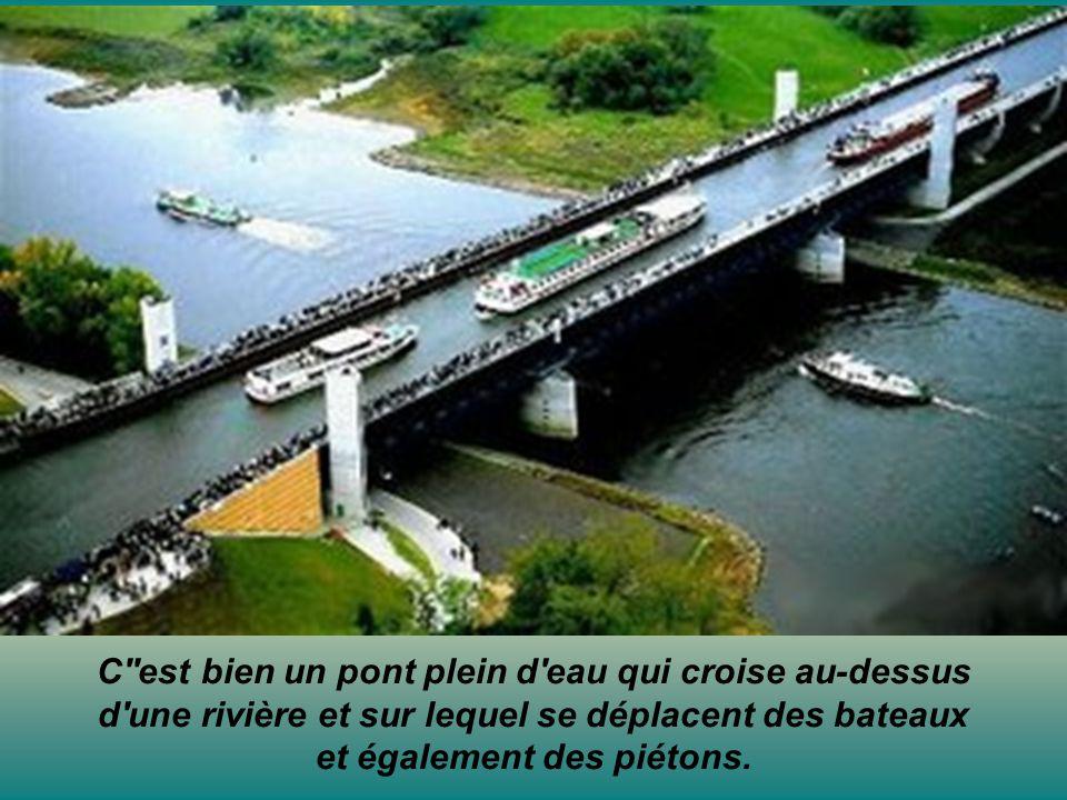 C''est bien un pont plein d'eau qui croise au-dessus d'une rivière et sur lequel se déplacent des bateaux et également des piétons.