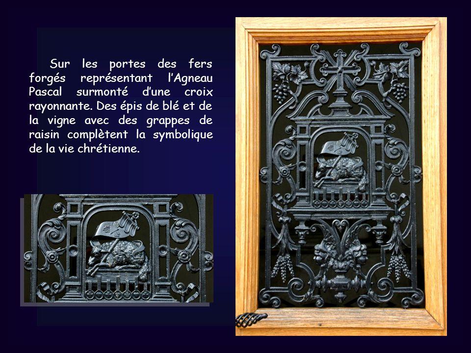 Sur les portes des fers forgés représentant lAgneau Pascal surmonté dune croix rayonnante.