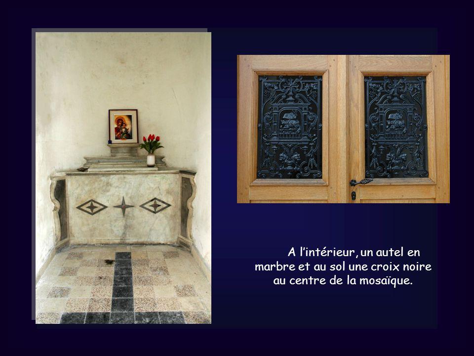 A lintérieur, un autel en marbre et au sol une croix noire au centre de la mosaïque.