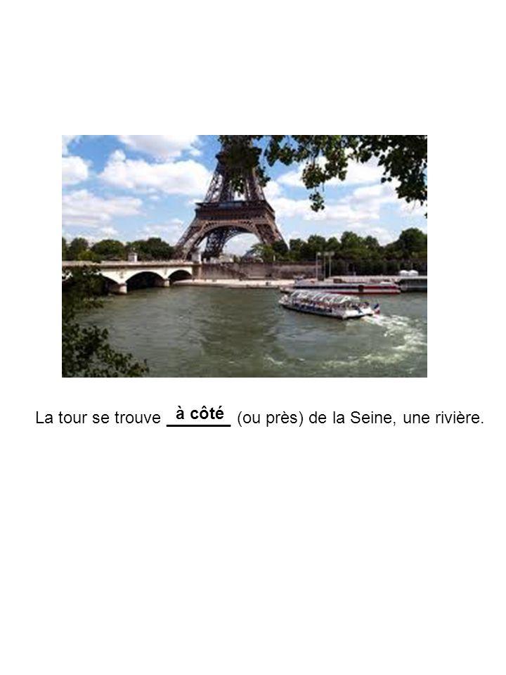 La tour se trouve _______ (ou près) de la Seine, une rivière. à côté