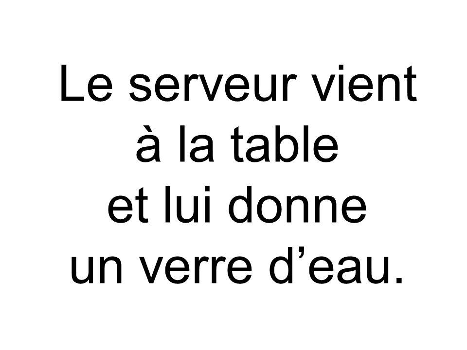 Le serveur vient à la table et lui donne un verre deau.